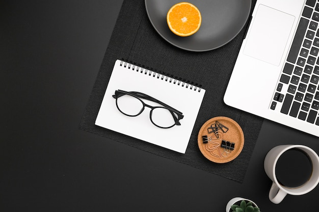 Flat lay of workstation with glasses on top of notebook and laptop