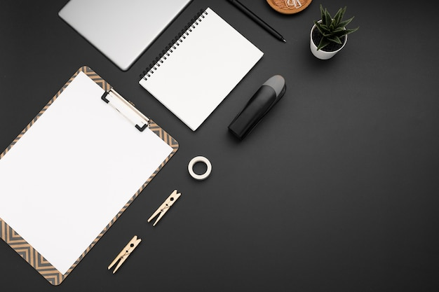 Flat lay of workstation with notepad and plant