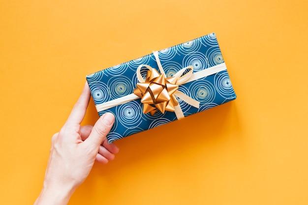 Flat lay wrapped birthday present on orange background