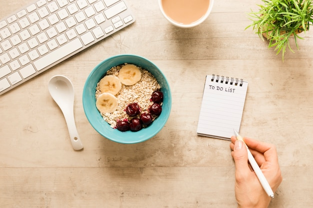Flat lay and writing in notebook near bowl with oats and fruits