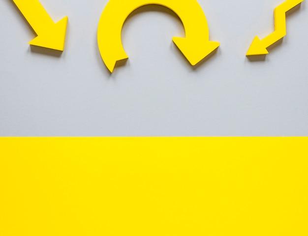 Frecce e cartone gialli di disposizione piana su fondo bianco