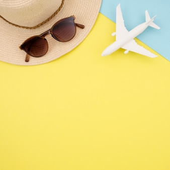 Flat lay of yellow background with hat and glasses