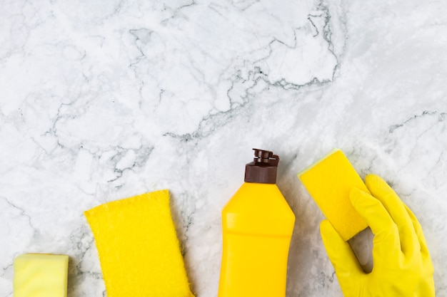 Flat lay yellow cleaning products with glove