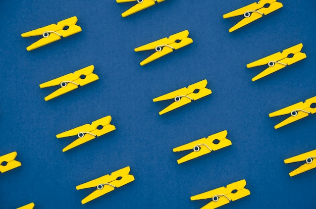 Flat-lay yellow clothes pins on blue background