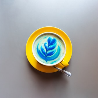 Flat lay of yellow hot trendy blue latte with art flower petals on the foam