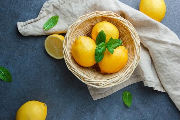 暗い表面の白い布の上に黄色いレモンと葉をバスケットに平らに置きます。水平