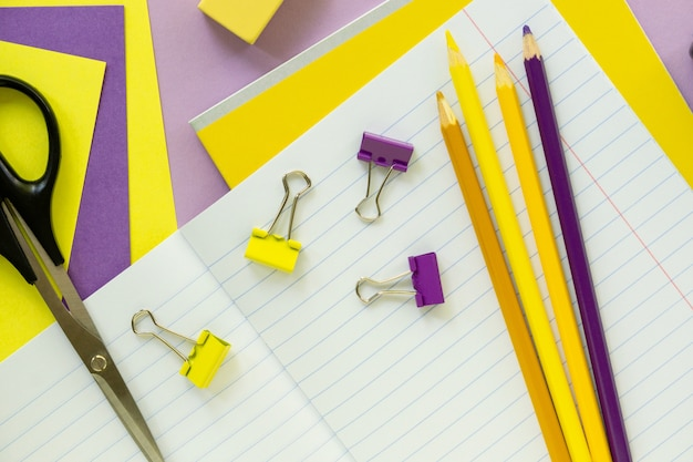 Flat lay of yellow and lilac school supplies