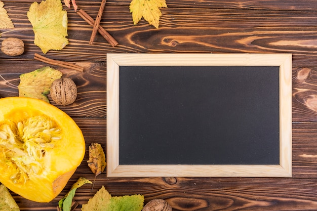 Flat lay yellow pumpkin and modern frame with mock-up