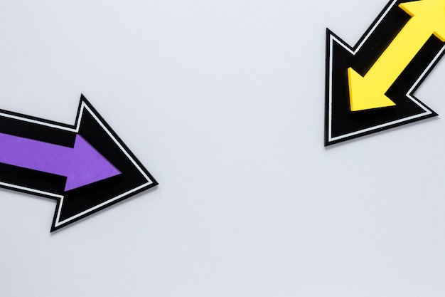 Flat lay yellow and purple arrows on white background
