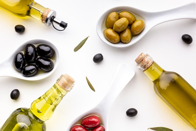 Flat lay yellow red black olives in spoons with oil bottles
