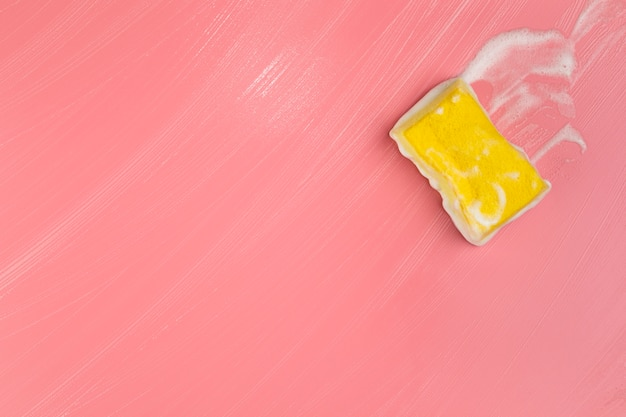 Flat lay yellow sponge with foam on pink background