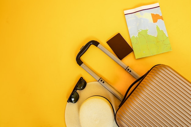 Flat lay yellow suitcase with traveler accessories sunglasses on yellow background