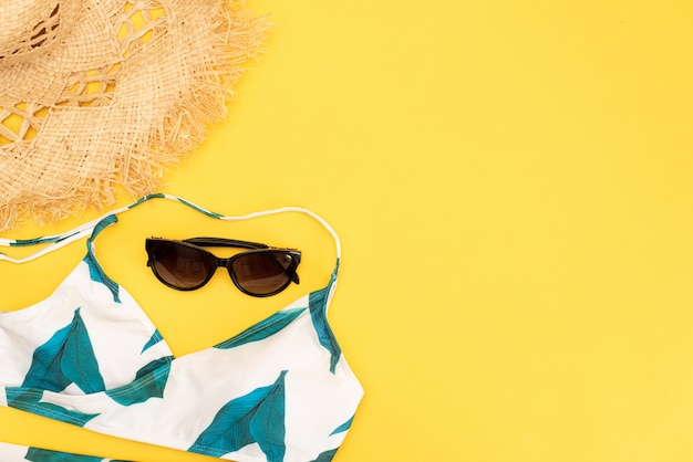 Flat lay yellow suitcase with traveler accessories on yellow background.
