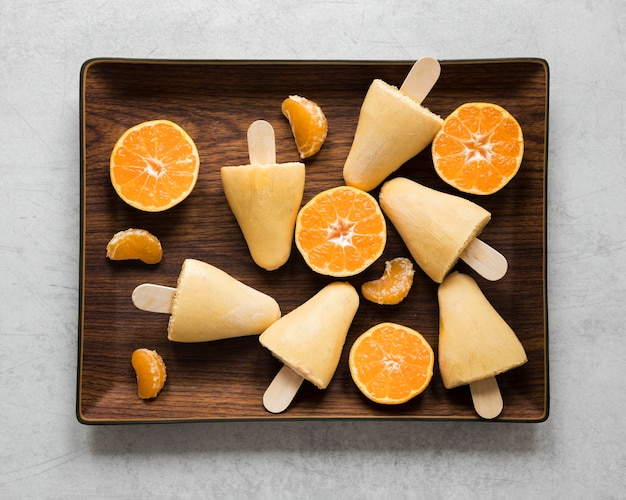 Flat lay of yummy orange flavored popsicles