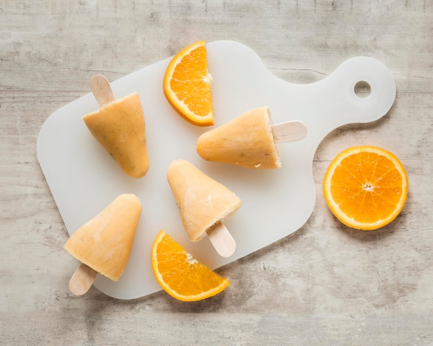 Flat lay of yummy popsicles on chopping board with orange
