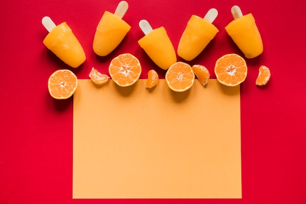 Flat lay of yummy popsicles with copy space and oranges