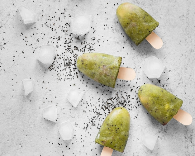 Flat lay of yummy popsicles with poppy seeds and ice