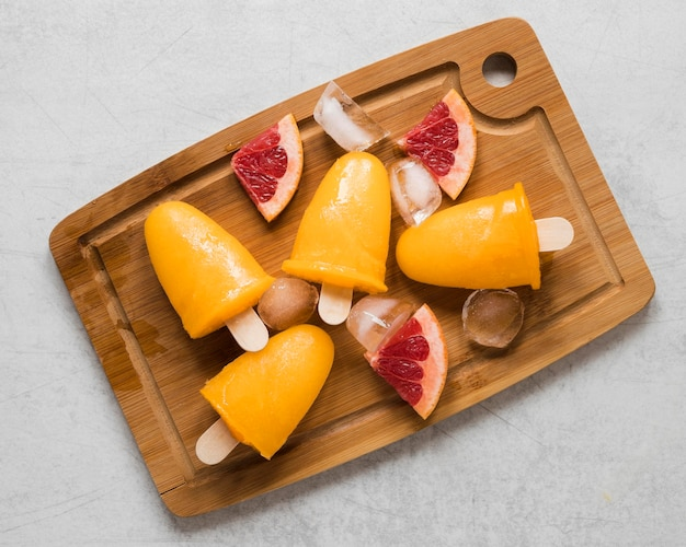 Flat lay of yummy red grapefruit flavored popsicles on chopping board