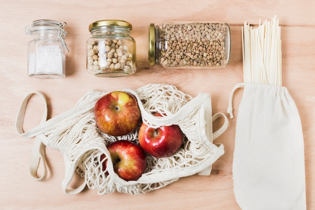 Flat lay zero waste assortment on wooden background with apples
