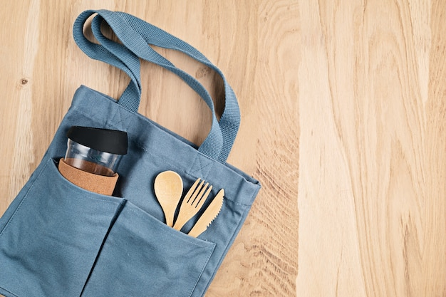 Flat lay of zero waste kit. set of eco friendly bamboo cutlery, cotton bag. sustainable, ethical, plastic free lifestyle. top view