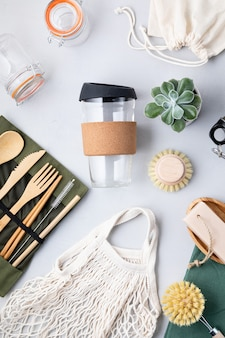 Flat lay of zero waste kit. set of eco friendly bamboo cutlery, mesh cotton bag, reusable coffee tumbler, brushes, bar soap and water bottle. sustainable, ethical, plastic free lifestyle