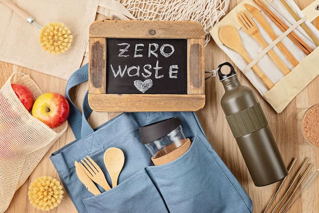 Flat lay of zero waste kit. set of eco friendly bamboo cutlery, mesh cotton bag, reusable coffee tumbler, brushes and water bottle. sustainable, ethical, plastic free lifestyle. top view