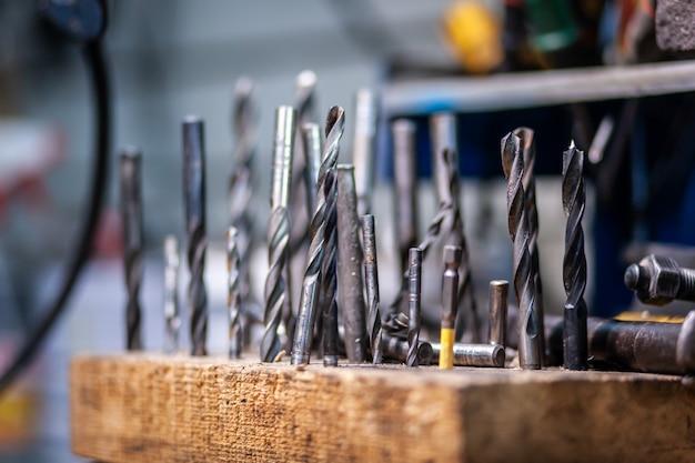 Flat lay металлические инструменты. набор сменных металлических сверл разных размеров и других инструментов находится в ящике для инструментов, вид сбоку.