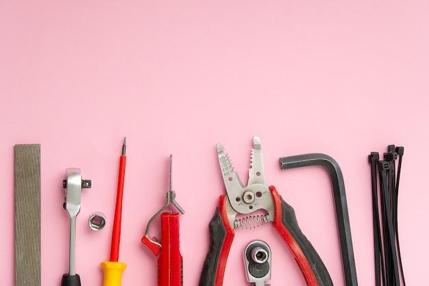 Flat lay из набора инструментов для домашнего ремонта на розовом фоне