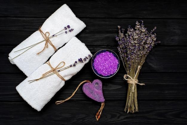 Концепция спа. лавандовая соль для расслабляющей ванны, мыло ручной работы, белые полотенца и сухие цветы лаванды на черном деревянном фоне. ароматерапия flat lay.