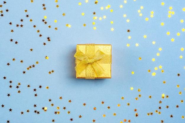 Золотая подарочная коробка и блестки в виде звездочек на синем фоне flat lay
