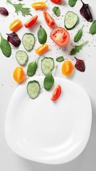 白い背景の上に空の白いプレートと平らな層状の新鮮な野菜、ハーブ、スパイス。