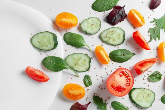 Плоские слоистые свежие овощи, травы и специи с пустой белой тарелкой на белом фоне.