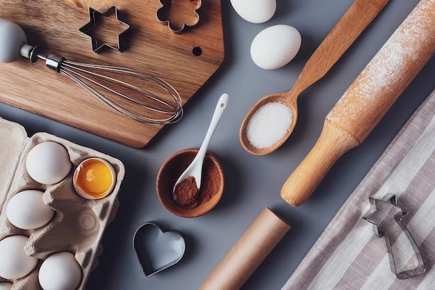 회색 배경에 평평한 레이아웃 구성, 베이킹 재료 및 주방 용품. 요리 유행 배경입니다. 휴가를 위한 수제 디저트를 만드는 개념.