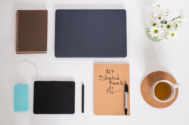 Flat layout of cup of green tea, white flowers in jug, sketchbook with highlighter, pad with stylus, notebook and folded laptop on desk