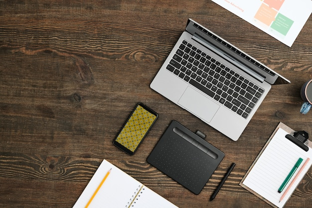 Flat layout of mobile gadgets, drink, open notebook with pencil and clipboard with working document and highlighter on wooden table