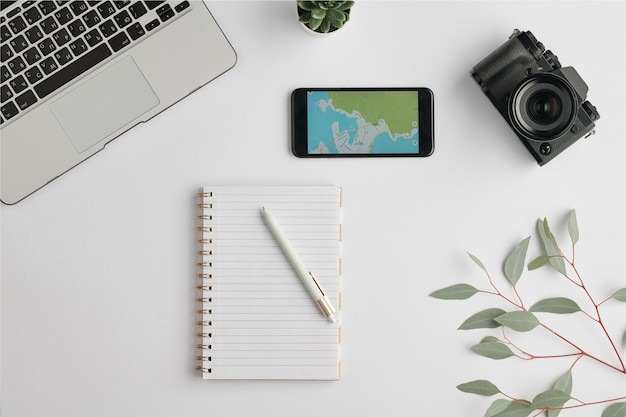 Flat layout of notebook with pen surrounded by smartphone, photocamera, laptop and branch with green leaves