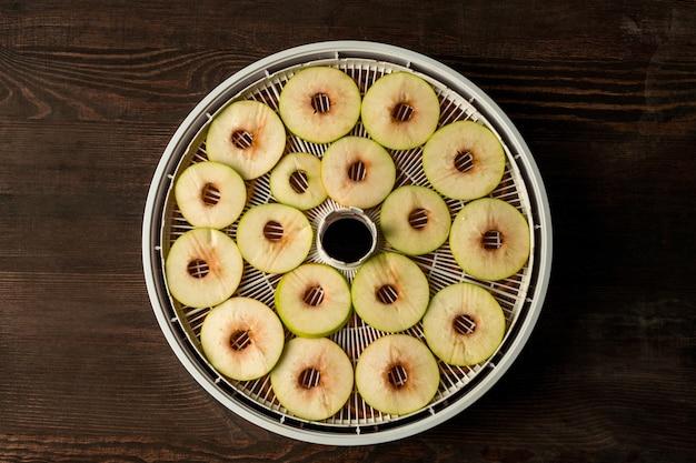 茶色の木製テーブルの上に新鮮なリンゴのスライスとフルーツ乾燥機の円形プラスチックトレイのフラットレイアウト