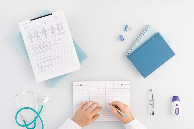 Плоский макет рук современного врача с ручкой над медицинской карточкой, собирающейся записывать информацию о пациенте по месту работы