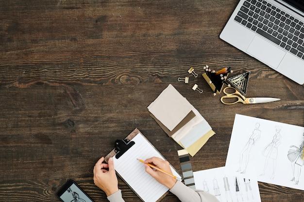 Плоский макет рук молодого модельера с карандашом на чистый лист бумаги в буфер обмена во время работы над новой коллекцией за деревянным столом