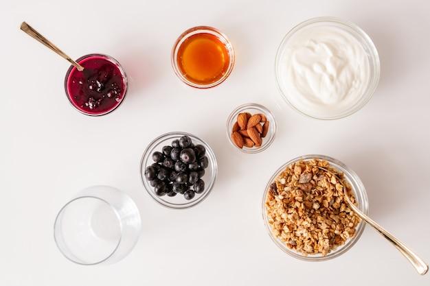 ミューズリー、チェリージャム、サワークリーム、アーモンドカーネル、蜂蜜、新鮮なブラックベリーを含むいくつかのボウルと白いキッチンテーブルのフラットレイアウト