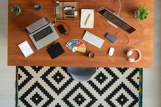 Плоский макет деревянного стола с компьютерным монитором, ноутбуком, цветовой палитрой, клавиатурой и мышью, планшетами, наушниками, напитками и другими принадлежностями