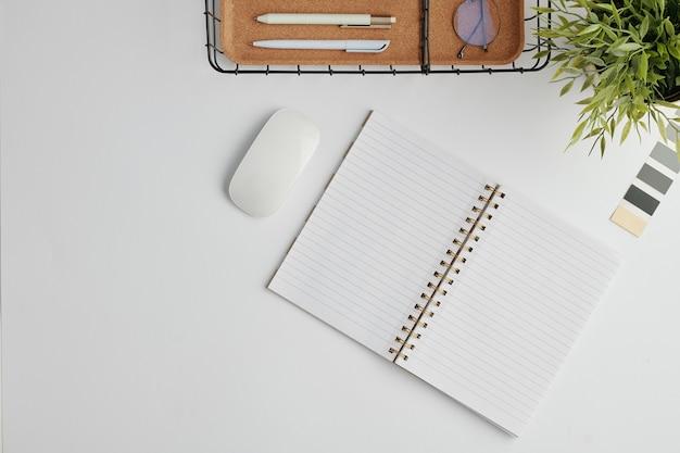 Плоский макет с компьютерной мышью, открытый блокнот с пустыми страницами, палитра. корзина для ручек и зеленых домашних растений в цветочном горшке на столе