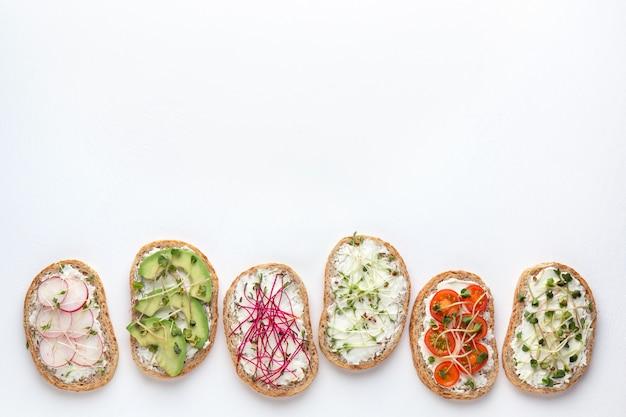 Плоский макет с различными бутербродами с овощами и микро зеленью на белом фоне