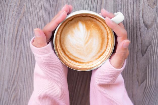플랫은 겨울에 추운 날에 나무 배경에 스웨터 손잡이로 부드럽게 뜨거운 커피 컵을 낳습니다.