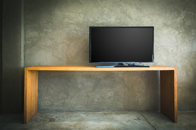 Flat lcd television on wood table in the living room with grunge concrete wall and parquet floor