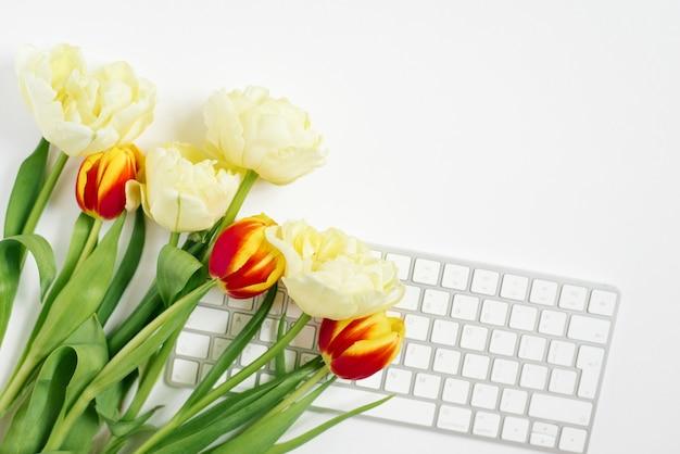 コンピューターのキーボードとチューリップの花束と平らな横たわっているバレンタインデーの背景。春の上面図。コピー用の空白