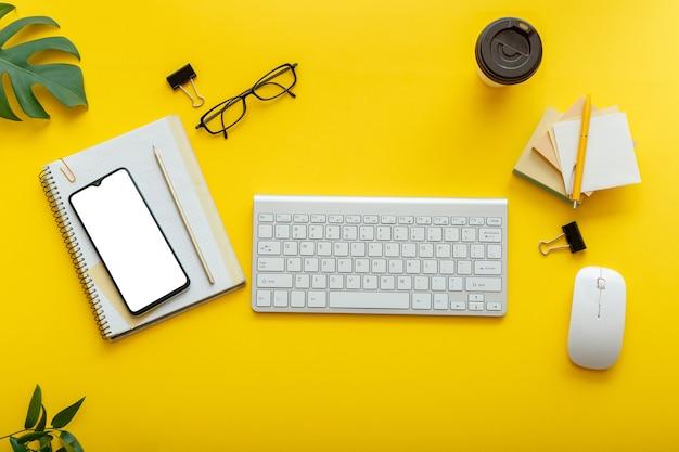 화려한 노란색 배경에 플랫 사무실 작업 공간입니다. 컴퓨터 키보드, 안경, 스마트폰 마우스, 사무용품 식물, 커피 컵이 있는 사무실 테이블 책상. 평면 누워 모형 전화 화면입니다.