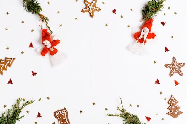 흰색 바탕에 빨간 크리스마스 장식, 진저브레드, 침엽수 가지가 있는 플랫 패턴입니다. 크리스마스 프레임 장식 배경입니다. 플랫 레이 디자인. 메리 크리스마스 크리스마스 배경입니다.
