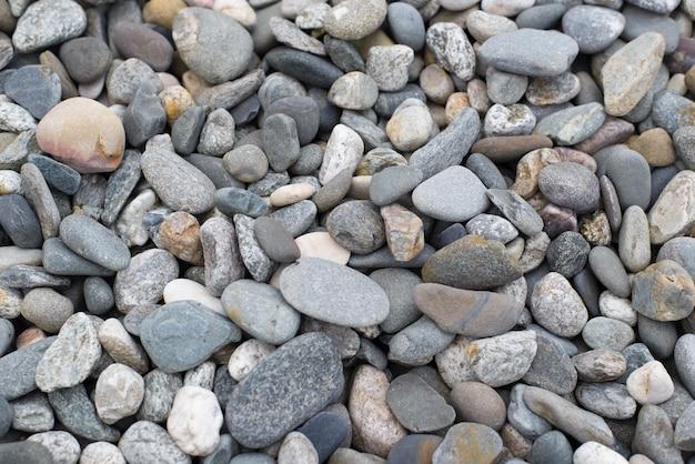 平らな小石のテクスチャの天然石の背景、上面図。庭やビーチの装飾に使用される、さまざまな色とサイズの平らな石