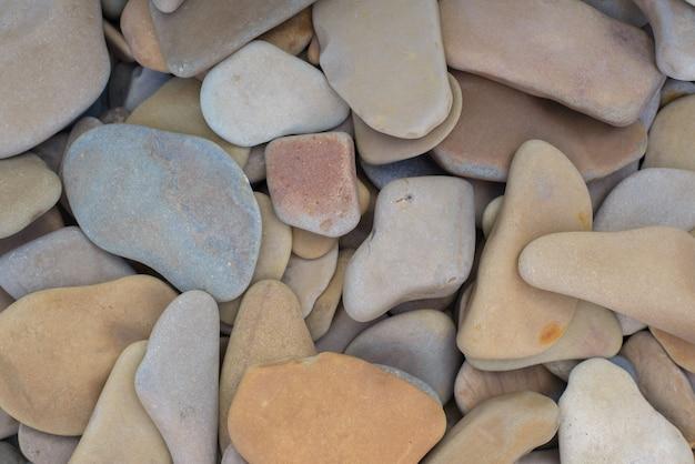 平らな小石のテクスチャの天然石の背景、上面図。平らな石は庭やビーチの装飾に使用されます
